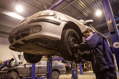 Auto mechanic repairs a car in a garage. Royalty Free Stock Photography