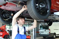 Auto mechanic repairs vehicle in a workshop. Brakes and tire stock photos