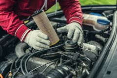 The auto mechanic replaces the car`s oil filter.