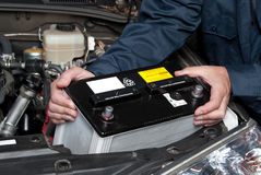 Auto mechanic replacing car battery. A car mechanic replaces a battery royalty free stock photos