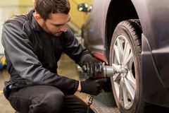 Auto mechanic with screwdriver changing car tire Stock Photos