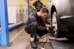 Auto mechanic with screwdriver changing car tire Royalty Free Stock Image