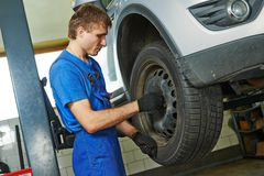 Auto mechanic screwing car wheel royalty free stock image