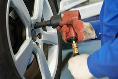 Auto mechanic screwing car wheel Royalty Free Stock Photos