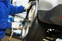 Auto mechanic screwing car wheel by wrench Stock Photos