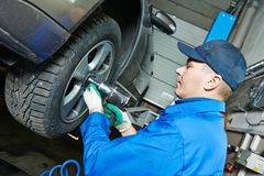 Auto mechanic screwing car wheel by wrench Stock Image