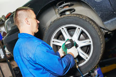 Auto mechanic screwing car wheel by wrench Stock Images