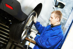 Auto mechanic screwing car wheel by wrench Royalty Free Stock Images