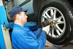 Auto mechanic screwing car wheel by wrench Stock Photo