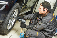 Auto mechanic screwing car wheel by wrench Royalty Free Stock Photo