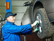 Auto mechanic screwing car wheel by wrench Stock Photography