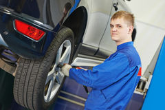 Auto mechanic screwing car wheel by wrench Royalty Free Stock Image