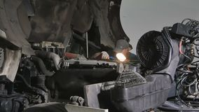 Auto mechanic seeks the breaking in motor. Auto mechanic repairs motor of truck at car service station. The man holds a lamp and lights it inside the engine of stock footage