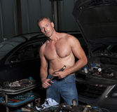 Auto mechanic. At service station with naked upper body Royalty Free Stock Image