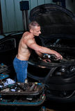 Auto mechanic. At service station with naked upper body Stock Images