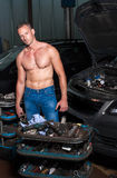 Auto mechanic. At service station with naked upper body royalty free stock images
