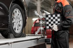 Auto mechanic sets the car for diagnostics and configuration. Wheel alignment equipment on a car wheel in a repair. Station stock image
