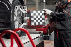 Auto mechanic sets the car for diagnostics and configuration. Wheel alignment equipment on a car wheel in a repair. Station royalty free stock photos