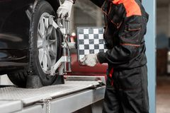 Auto mechanic sets the car for diagnostics and configuration. Wheel alignment equipment on a car wheel in a repair. Station royalty free stock photo