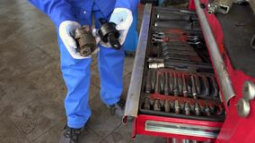 An auto mechanic showing a dirty used and new parts stock footage