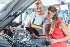Auto mechanic showing to a customer the engine error codes. Reliable auto mechanic showing to a female customer the engine error codes scanned by a car royalty free stock photos