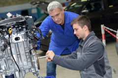 Auto mechanic shows trainee maintenance car engine. Auto mechanic shows trainee maintenance of car engine Royalty Free Stock Photography