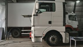 Mechanic prepares to tilt cabin of truck. Auto mechanic sits on crouches near the truck in car service station. The man raise the cabin of truck. Tilting the stock video footage