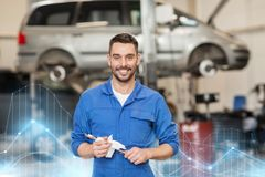 Auto mechanic or smith with wrench at car workshop. Car service, repair, maintenance and people concept - auto mechanic man or smith with wrench at workshop Royalty Free Stock Images