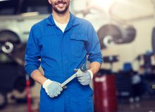 Auto mechanic or smith with wrench at car workshop stock photo