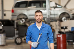 Auto mechanic or smith with wrench at car workshop Royalty Free Stock Image