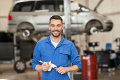 Auto mechanic or smith with wrench at car workshop Stock Photography