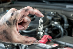 Auto mechanic and sparkplug. An auto mechanic holds an old, dirty sparkplug over a car engine he is tuning up royalty free stock photos