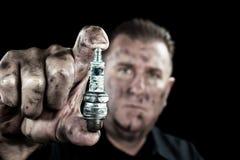 Auto mechanic and sparkplug royalty free stock photo