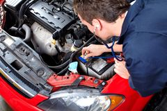 Auto mechanic with a stethoscope . Auto mechanic checking a vehicle. Car repair service