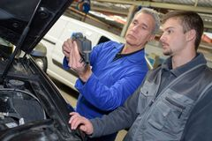 Auto mechanic teacher and trainee performing tests at mechanic school. Auto royalty free stock photos