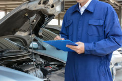 Auto mechanic (or technician) checking car engine Stock Image
