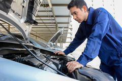 Auto mechanic (or technician) checking car engine Stock Photos