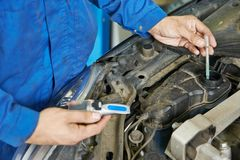 Auto mechanic tests car antifreeze liquid Royalty Free Stock Photos