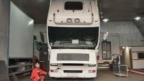 Auto mechanic tilting cabin of truck. Auto mechanic sits on crouches near the truck in car service station. The man raise the cabin of truck. Tilting the cabin stock video footage