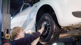 Auto mechanic is twisting manually bolts of a wheels on an automobile, raised by lifting equipment in auto-service. Workshop, tire works stock video