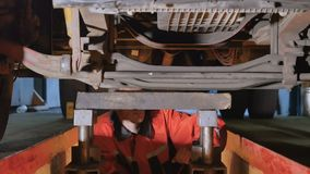 Auto mechanic view the bottom of truck. Auto mechanic is under the bottom of truck. Professional worker checks the parts of truck from the down. Man views left stock video footage