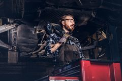 Mechanic in a uniform and safety glasses holds an angle grinder while standing under lifting car in a repair garage. Auto mechanic in a uniform and safety Stock Images
