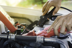 Auto mechanic uses a charging battery with electricity trough ju Royalty Free Stock Photo