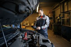 Auto mechanic uses a multimeter voltmeter to check the voltage level in a car battery. royalty free stock photo