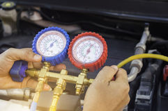 Auto mechanic uses a pressure gauge on the air compressor,liquid. Air pressure,compressor,manometer in a car,Selective focus Stock Photos