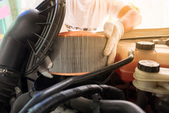 auto mechanic wearing protective work gloves holding a dirty Stock Image