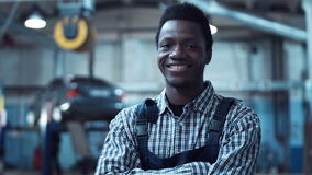 Auto mechanic wearing striped shirt smiles