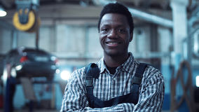 Auto mechanic wearing striped shirt smiles. At camera as he stands with arms crossed stock photography
