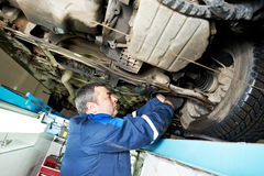 Auto mechanic at wheel alignment work with spanner. Car mechanic tighten in make suspension adjustment with spanner during automobile wheel alignment work at stock image