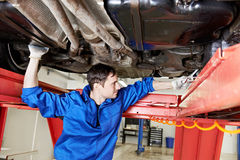 Auto mechanic at wheel alignment work with spanner. Car mechanic tighten screw in make suspension adjustment with spanner during automobile wheel alignment work Stock Photography